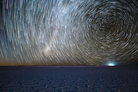 Salar de Uyuni salt flat under night starry sky with star trails like a comets. Altiplano, Bolivia