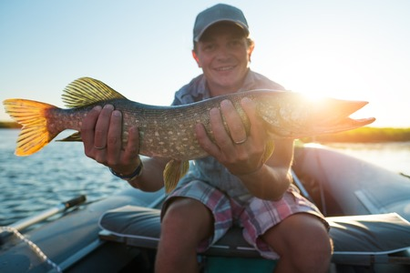 Young amateur angler sits in the boat on a river and holds pike
