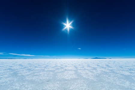Salar de Uyuni salt flat with salt patterns and blue clear sky. Bolivia