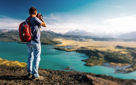 Photographer stands on top of a hill and takes photo of the valley with blue lake. Torres del Paine National Park, Chile. Tilt shift effect applied, edges are out of focus.