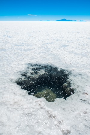 Hole with salty water in the middle of the Salar de Uyuni, Bolivia Stock Photo