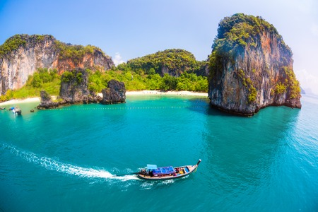 Traditional Thai longtail boat moves in front of the island of Hong and its perfect calm lagoon with white sand beach, Thailand