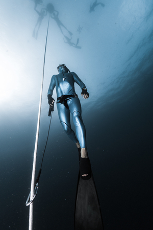 Freediver ascends from a depth along the rope holding a safety leash in a hand. Freedive instructor prepares freedive spot for session, while studens wait on the sea surface