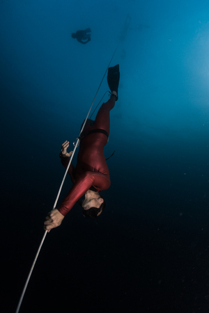 Freediver in red wetsuit descends along the rope. Safety freediver follows him on the background.