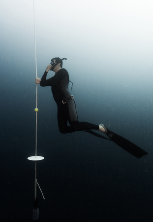 Student freediver learns presure equalization being on a depth and holding a rope