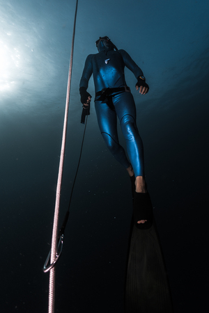 Freediver ascends from a depth along the rope holding a safety leash in a hand. Stock Photo