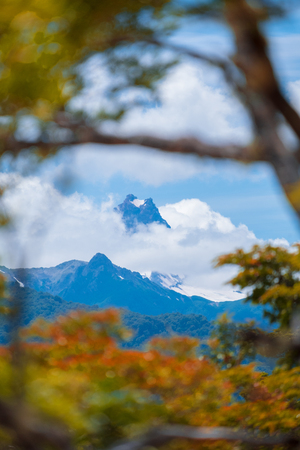 Snow capped mountain covered with clouds and lush trees on the foreground. Patagonia, Chile 写真素材