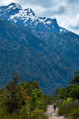 Woman walks on the hiking trail in a park with lush green trees and snow capped mountains on the background. Patagonia, Chile Stock Photo