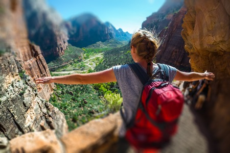 Woman hiker stands with raised hands and enjoys the valley view in the Zion National Park, USA