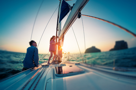 Couple works with ropes on the sail boat at sunset. Tilt shift effect applied Imagens