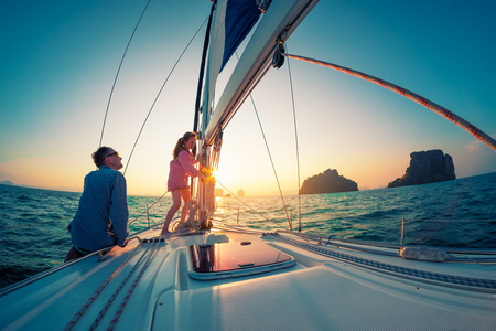 Couple of young sailors, man and woman, works with rope on the bow of the sailing boat at sunset Imagens