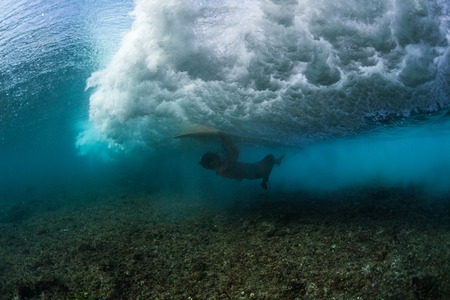 Surfer perform trick named in surfing as Turtle Roll to safely pass the wave