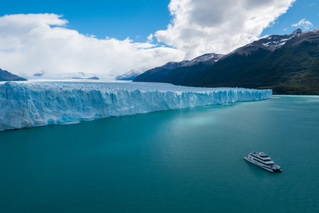Vorderer Teil des Perito-Moreno-Gletschers im südpatagonischen Eisfeld und touristisches Tagesausflugboot auf dem türkisfarbenen Lago Argentino. Argentinien