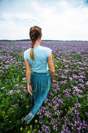 Woman in a dress walks on the summer meadow full of purple flowers