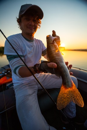 Young angler holds the fish (Zander) sitting in a boat at a lake during sunset