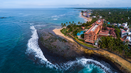 Aerial panorama of the coastline with resorts in the town of Hikkaduwa during low tide, Sri Lanka