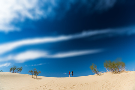 Couple of hikers walks on the sandy desert. The Death Valley, USA. Tilt shift effect applied