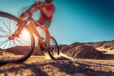 Man rides bicycle in the desert. Tilt shift effect applied Stock fotó