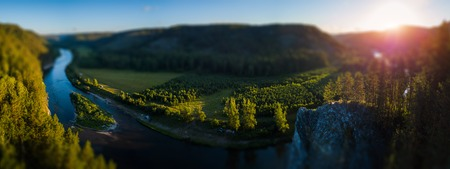 Aerial panorama of the Ural Mountains and the river of Belaya during sunrise. Russia. Tilt shift effect applied
