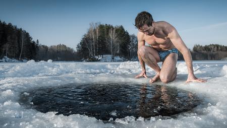 Joven sano va a nadar en un agujero de hielo en el lago de invierno