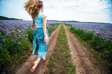 Woman in a dress runs barefoot on the rural road along the summer meadow full of purple flowers Zdjęcie Seryjne
