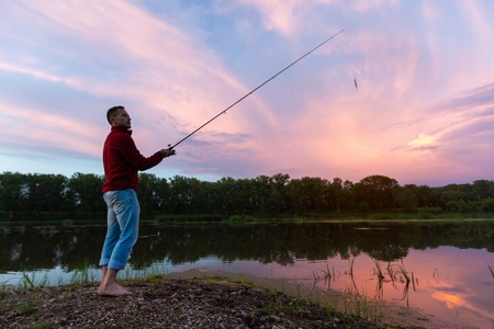 Amateur angler fishing on the coast of a shallow river with a surface floating lure during sunset
