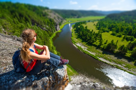 Woman hiker sits on the rock and enjoys the river flowing in the valley. Ural Mountains and the River of Belaya, Russia