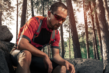 Tired trail running athlete having a rest in the forest 写真素材