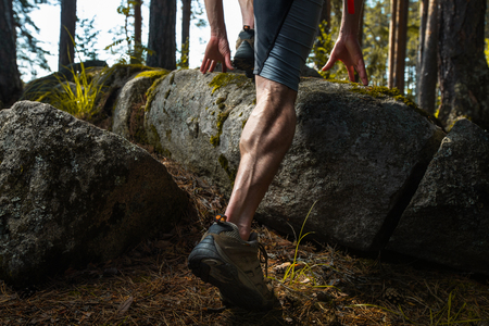 Muscled leg of the trail running athlete crossing rocky terrain in the summer forest
