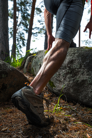 Muscled leg of a trail running athlete running in the forest