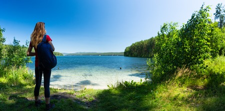 Hiker stands on the green coast of a crystal clear lake. Lake of Turgoyak, Russia