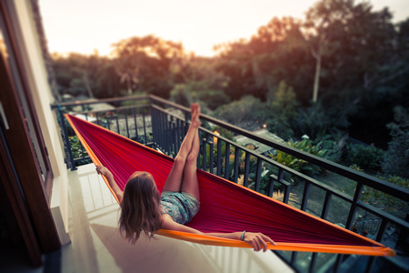 Woman relaxes in the hammock set on a balcony and enjoys sunset and tropical garden view. Tilt shift effect applied Stock fotó - 116955339