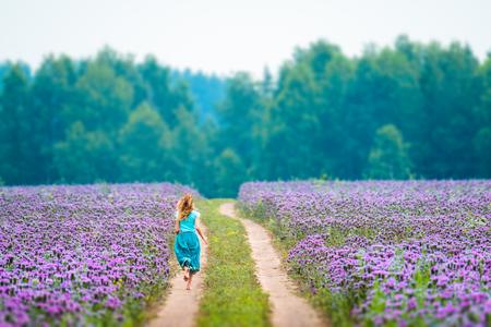 Woman runs in the field with purple flowers Zdjęcie Seryjne