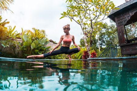 Young woman performs yoga exersices in the tropical garden near the pool