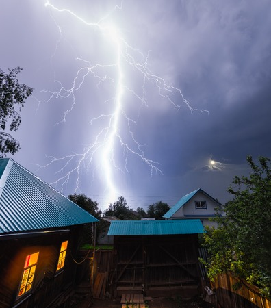 Thunderbolt in the night sky over the village with houses and garden Archivio Fotografico