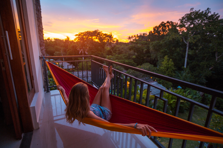 Woman relaxes in the hammock set on a balcony and enjoys sunset and tropical garden view