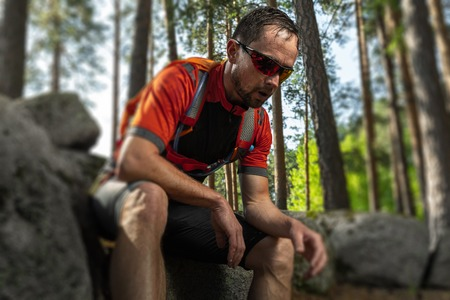 Tired trail running athlete having a rest in the forest. Tilt shift effect applied Stock fotó