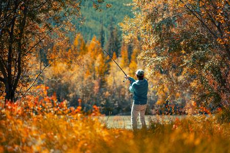 Pescador aficionado a la pesca en el río de otoño