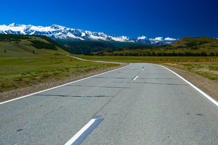 Asphalt road and mountains on the horizon. Chuysky Trakt - M52. Altai, Russia