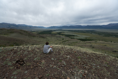 Young man sits on the hill and observes the valley. Altai Republic, Russia