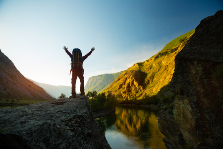Hiker with backpack stands on a cliff with raised hands during sunrise Stok Fotoğraf