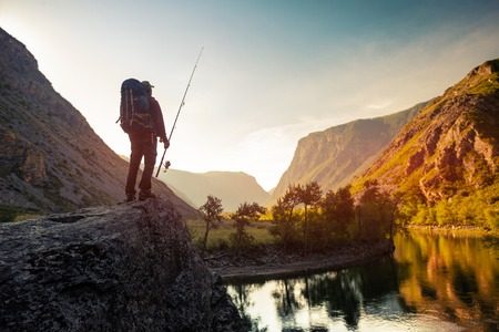 Hiker stands on the rock with backpack and fishing rod and enjoys sunrise river view