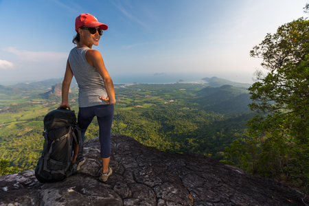 Lady hiker stands on the cliff with backpack and smiles.