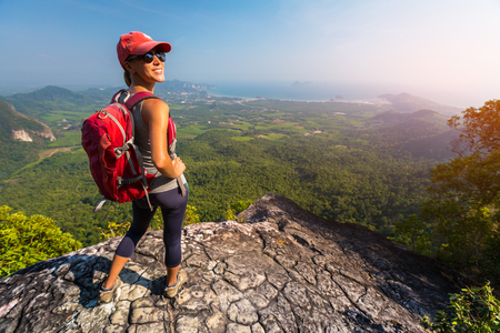 Woman hiker stands on top of the mountain and smiles and looks into camera Banque d'images - 116950236