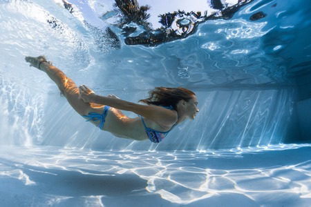 Young woman glides underwater in the pool on a sunny day Stok Fotoğraf