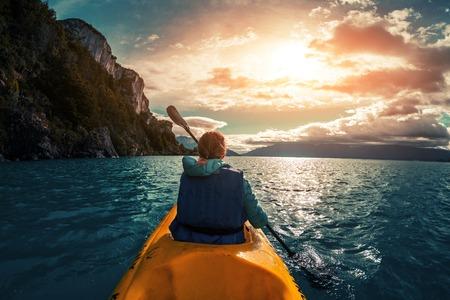 Woman paddles kayak on a lake. Chilean Patagonia