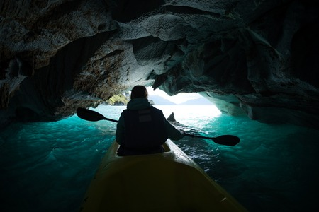 Woman paddles kayak inside the marble cave located on the General Carrera lake in Chile 写真素材 - 119277061