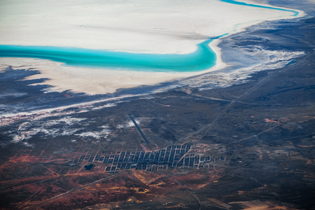 Aerial view of the town of Uyuni, Bolivia. Entrance to the Uyuni Salt Flat is visible on upper part of the frame as dark radial tracks on white salt surface. Banco de Imagens - 119276888