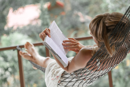 Woman in summer dress lies in the hammock in a garden and reads the book Banco de Imagens
