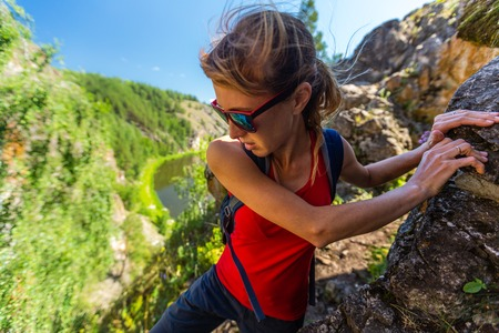 Woman hiker climbs the rocky cliff